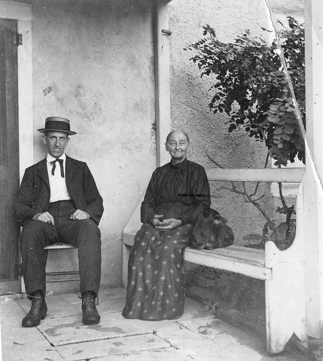 Edwin C. Jellett, in suit and bow tie, sitting on flagstone porch with an unidentified woman; estimated date (1910); Germantown Historical Society