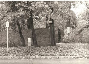 Signs, trees, and stone wall