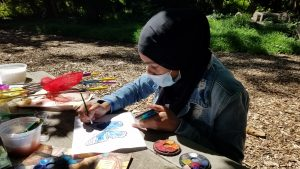girl painting a blue butterfly