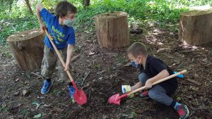 two boys digging in dirt with shovels