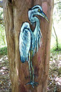 standing blue heron painted on tree