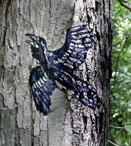 flying raven painted on tree