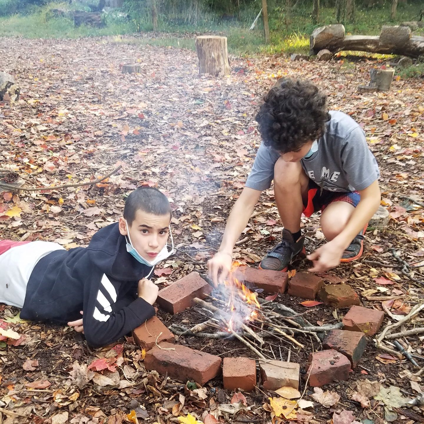 two boys building a campfire